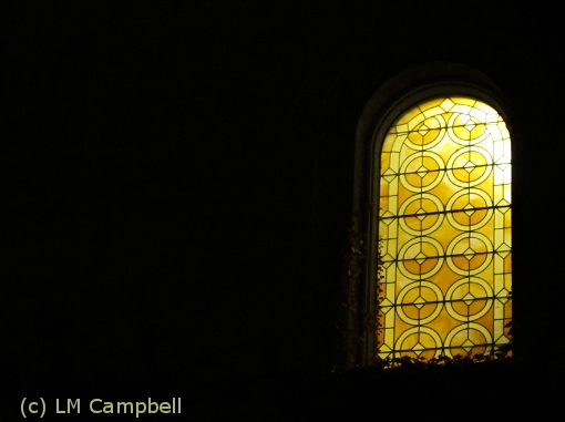 Yellow stained glass window at night