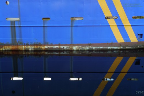 Yellow stripes on a ship reflecting on water create arrows