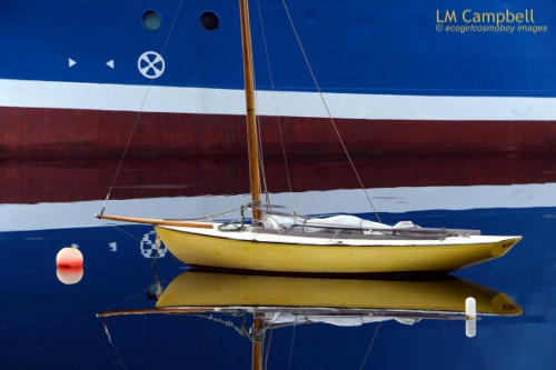 A yellow sailboat floating in the reflection of a large neighbouring ship